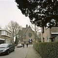 Overzicht van de westgevel met groot rondvenster met glas-in-lood boven de hoofdentree, gezien vanuit zijstraat - Hilversum - 20414436 - RCE.jpg
