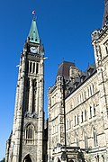 A tall, stone brick bell tower with a large clock in Ottawa, Canada