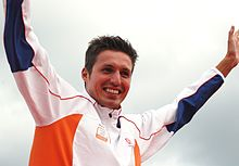 Man with spiky brown hair and stublle raises his arms aloft. He is wearing a white tracksuit top with blue and orange portions.