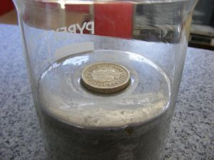 Buoyancy - A metallic coin (one British pound coin) floats in mercury due to the buoyancy force upon it and appears to float higher because of the surface tension of the mercury.