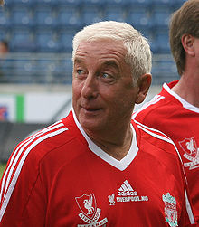 "The head and upper torso of a gentleman in his late 50s. He has short white hair and is wearing a red football shirt, which has the Liverpool F.C. crest on the left breast, and a crest on the right breast that says ""Liverpool Legends"". A white logo of the Adidas sponsor is visible in the centre of the shirt, and three white stripes are present on the shoulder."