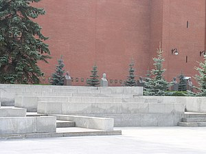 Kremlin Wall Necropolis - Tombs of Suslov, Stalin, Kalinin, Dzerzhinsky, Brezhnev in front of the Kremlin wall. Tomb of Yuri Andropov, which stands between Kalinin's and Dzerzhinsky's, is obstructed by trees. The Mausoleum is immediately to the right.