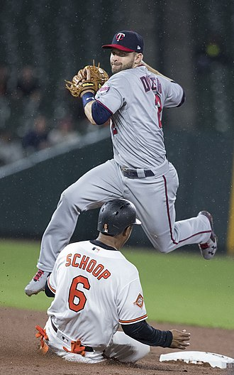 Baseball field - Brian Dozier of the Minnesota Twins leaps over a sliding Jonathan Schoop of the Baltimore Orioles attempting to turn a double play