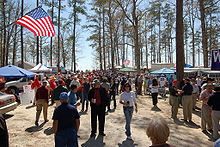 People stroll in a wooded area decorated with American flags.