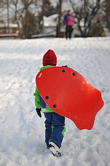 canadian child carrying his modern toboggan december