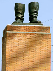 a tan brick pedestal supporting a pair of bronze statue boots with nothing attached