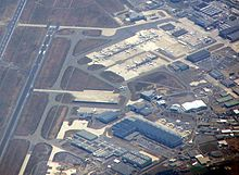 View from the air. Runway to the left and bottom. To the right long buildings and lots of aircraft.