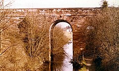 A tall, brown stone bridge with one wide central arch over a canal, and a secondary arch over a towpath. The bridge is partially obscured by trees.