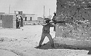 A man aims a rifle from around the corner of a bullet-scarred wall. In the background another man is attempting to take cover behind a low wall and partial door.