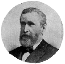A black and white circular portrait of a Caucasian man in a suit and bow tie.