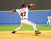 "A left-handed baseball pitcher wearing a black baseball cap, white uniform, and black shoes; the back of his uniform has the lettering ""GLAVINE"" and the number 47, in a throwing stance."