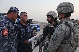 5th Field Artillery Regiment - Two soldiers from the 1st Battalion, 5th Field Artillery Regiment speaking with Iraqi police in August 2011