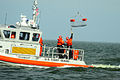 U.S. Coast Guardsmen aboard a response boat catch a rescue basket lowered by a MH-65C Dolphin helicopter crew as part of a training evolution on Lake Pontchartrain, La., Jan 120117-G-BD687-006.jpg