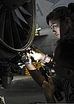 U.S. Navy Aviation Machinist's Mate 2nd Class Sovannara Dy, top, and Aviation Machinist's Mate 3rd Class Rochel Roque, both with Strike Fighter Squadron (VFA) 146, perform maintenance on an aircraft engine 130819-N-KE148-125.jpg