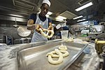 U.S. Navy Culinary Specialist Seaman Timothy Vernon makes pretzels in the galley of the guided missile destroyer USS Arleigh Burke (DDG 51) March 8, 2014, in Marseille, France 140308-N-WD757-026.jpg