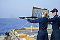 U.S. Navy Fire Controlman 3rd Class Kelsey Baker, center, fires a 12-gauge shotgun while Gunner's Mate 2nd Class William Tedder supervises during a small-arms qualification aboard the guided missile cruiser 131105-N-QL471-1130.jpg