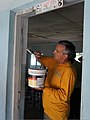 U.S. Navy Master Chief Information Systems Technician Andrew Key, assigned to the High Speed Vessel Swift (HSV 2), paints the doorway of a classroom at the Kinondi Muslim High School during a community relations 120629-N-JL721-049.jpg