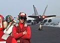US Navy 021203-N-9593M-045 An Ordie (Aviation Ordnanceman) stands by as an F-A-^8E Super Hornet launches.jpg