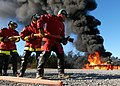 US Navy 040211-N-6901L-005 A hose team of U.S. Coast Guardsman prepare to advance and engage a fire on a fire fighting trainer at the Naval Air Station Whidbey Island Fire School.jpg