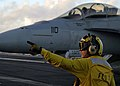 US Navy 041101-N-0499M-067 An Aviation Boatswain's Mate directs an F-A-18F Super Hornet.jpg