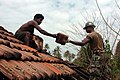 US Navy 050116-N-6843I-015 Builder Constructionman Sean Liverpool of Brooklyn, N.Y., assigned to Naval Mobile Construction Battalion Seven (NMCB-7), works alongside a local Sri Lankan man as they salvage tiles from the roof of.jpg