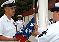 US Navy 070614-N-2555T-004 Senior Chief Electronics Technician David Fujioka and Personnel Specialist 1st Class Carrie Singleton prepare to raise the flag at Expeditionary Combat Readiness Center (ECRC) during a Flag Day ceremo.jpg