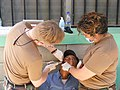 US Navy 090401-N-1580K-582 Navy dentist Cmdr. David Reiter and Hospital Corpsman 2nd Class Amy Brown remove an upper molar from a villager in Aguacatal during the Beyond the Horizon humanitarian assistance exercise in Honduras.jpg