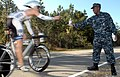 US Navy 091107-N-9936B-656 Hospital Corpsman Derrick Cooper, assigned to Operational Support Unit Wilmington, hands a water bottle to a competitor in the annual Beach2Battleship Triathlon.jpg