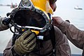 US Navy 091116-N-4154B-265 Navy Diver 1st Class Daniel Muhlbach completes his final pre-dive checks before diving down to secure a set of lifting wires to a sunken barge.jpg