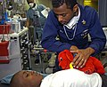 US Navy 100121-N-8366W-018 Electronics Technician 1st Class Dietrich Rey comforts a seven-year-old Haitian boy who is being treated aboard the Military Sealift Command hospital ship USNS Comfort (T-AH 20).jpg
