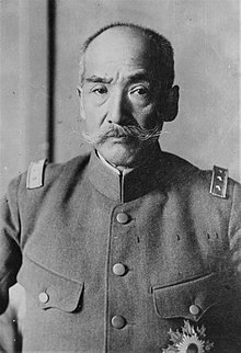 Photo en noir et blanc d'un homme asiatique en uniforme portant la moustache.