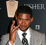 Usher, wearing a white shirt, criss-cross tie and chequered jacket, waving in front of his perfume branded wallpaper