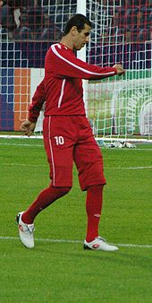 A photograph of a man in red association football attire.