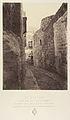 Ve Station. Jésus aidé par Simon de Cyrène. Une marque dans le mur indique seule cette station. La maison que l'on voit au fond est celle du mauvais riche MET DP345538.jpg