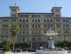 "A view of one of Viareggio's many grand hotels along the famous passeggiata, with the ""Fountain of the Four Seasons"" by Beppe Domenici in front."