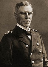 An older man in a double-breasted naval uniform
