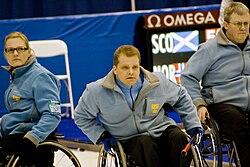 Três atletas em cadeira de rodas observam algo fora do alcance da imagem.