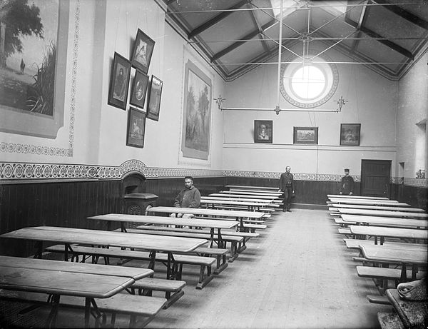 Interior of an asylum for the mentally ill, with few people, large tables and paintings on the walls