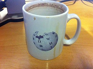 Photograph of stained and used coffee mug with Wikipedia Globe Logo on desk