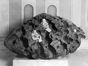 Meteorite weathering - Two children are sitting within the corrosion grooves of the Willamette meteorite. Considerable mass has been lost to terrestrial weathering.