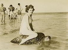 Young woman riding on the back of a turtle at Mon Repos Beach, near Bundaberg, ca. 1930