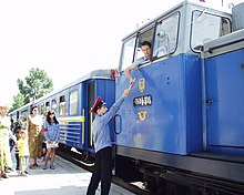 Blue train at a station, with the engineer passing a stick to employee on platform