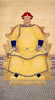 Full-face retrato de um homem corpulento com um mustachio fina vestindo um chapéu vermelho e um manto amarelo multicamadas com decorações dragão pintado, e sentado em um trono montado em um pódio baixa.