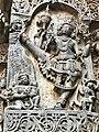 12th-century stone carving showing Vishnu avatar Vamana taking one of three steps legend at Shaivism Hindu temple Hoysaleswara arts Halebidu Karnataka India.jpg