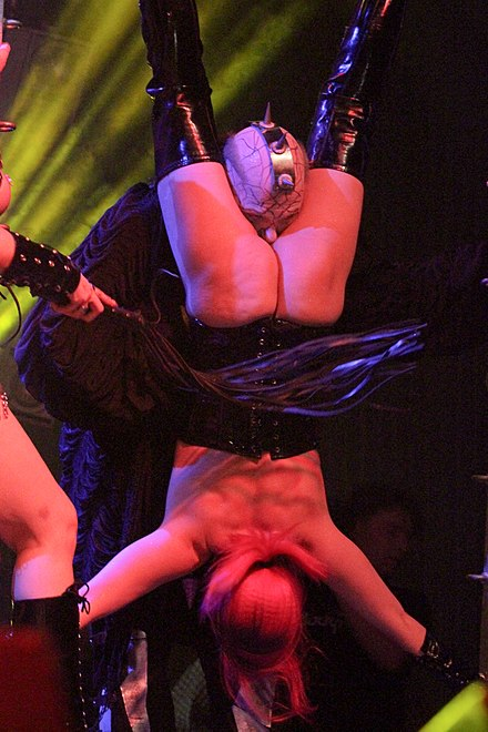 Sexual activity may occur in BDSM, but it is not essential part of BDSM. Photo shows erotic humiliation of sexual nature being performed at Wave-Gotik-Treffen music festival, Germany, 2014. The submissive woman is stripped naked, hung upside down, whipped and a master doing sexual roleplay of a devil forces himself on her to cause vagina torture. 2014 WGT 264 Umbra Et Imago.jpg