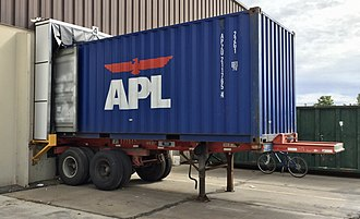 American President Lines - 20' APL container mounted onto a chassis parked at a loading dock in the United States.