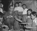 A U.S. Air Force airman distributes books to Thai children at Korat, Thailand. - NARA - 542307.tif