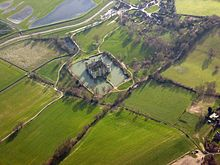 An aerial view of the Bodiam. The square castle is surrounded by a roughly square moat, and beyond that stretch green fields.