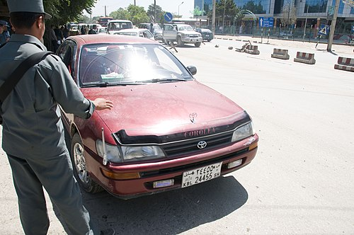 A Toyota Corolla (E100) at a security checkpoint in 2010 Afghan National Police set up Ring of Steel (4671626066).jpg