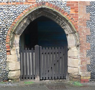 Blakeney Chapel - This arch in Cley is traditionally believed to have originally been part of Blakeney Chapel. The wall is of the flint and mortar type typical of this area.